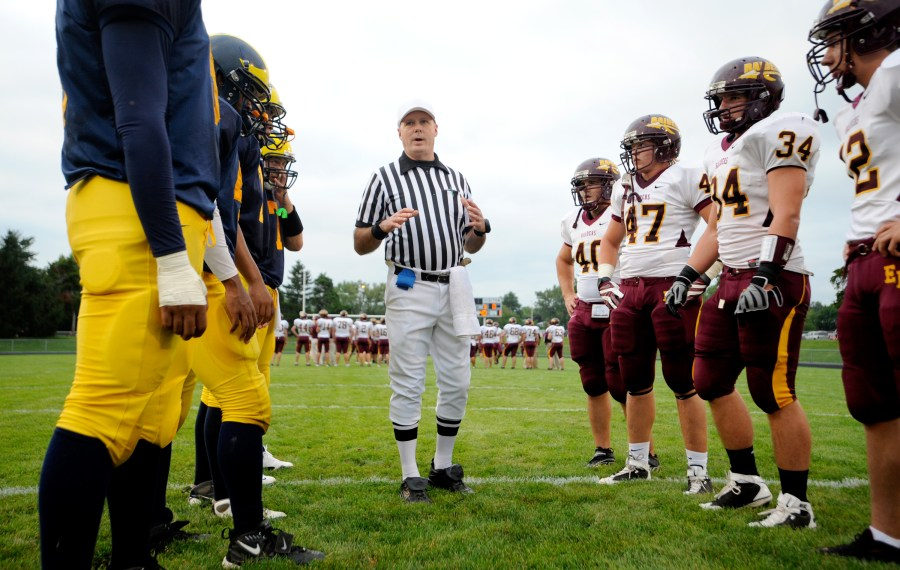 ADAM GERIK/JOURNAL STAR  The Woodruff Warriors and East Peoria Raiders meet face to face at the start of Friday's game at Peoria Stadium.