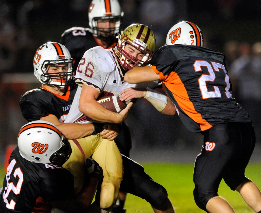 RON JOHNSON/JOURNAL STAR   Washington's Marquise Hartl, left, Connor Underwood, and Jeremy Cannon, right, join forces to bring Dunlap running back Caleb Miller down during the second half of Friday's game at Washington.