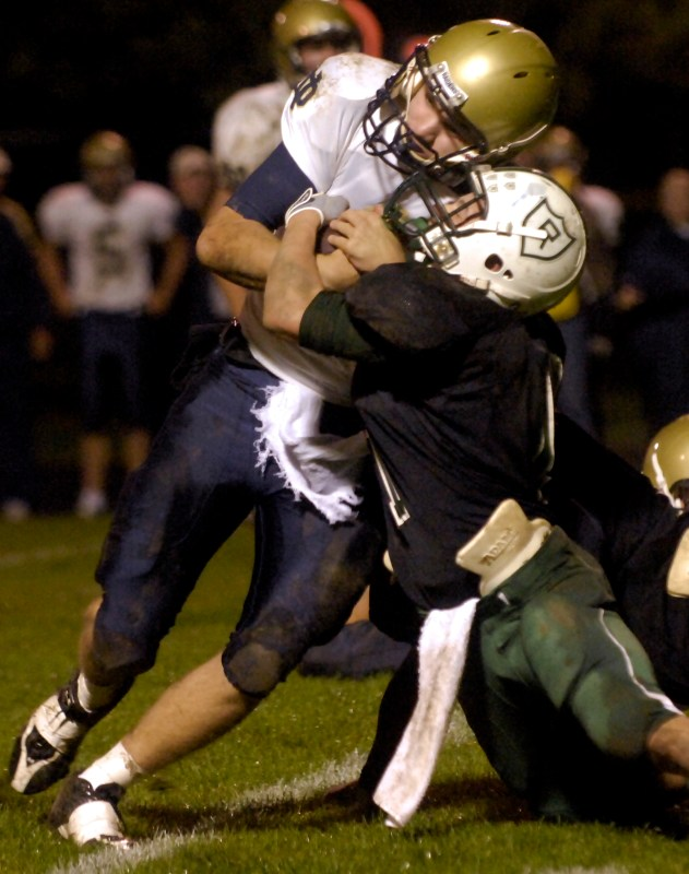 MATT DAYHOFF/JOURNAL STAR  Richwoods' Noah Moore, right, brings down Quincy Notre Dame running back Conner McLaughlin in the first half Friday night at Richwoods High School.