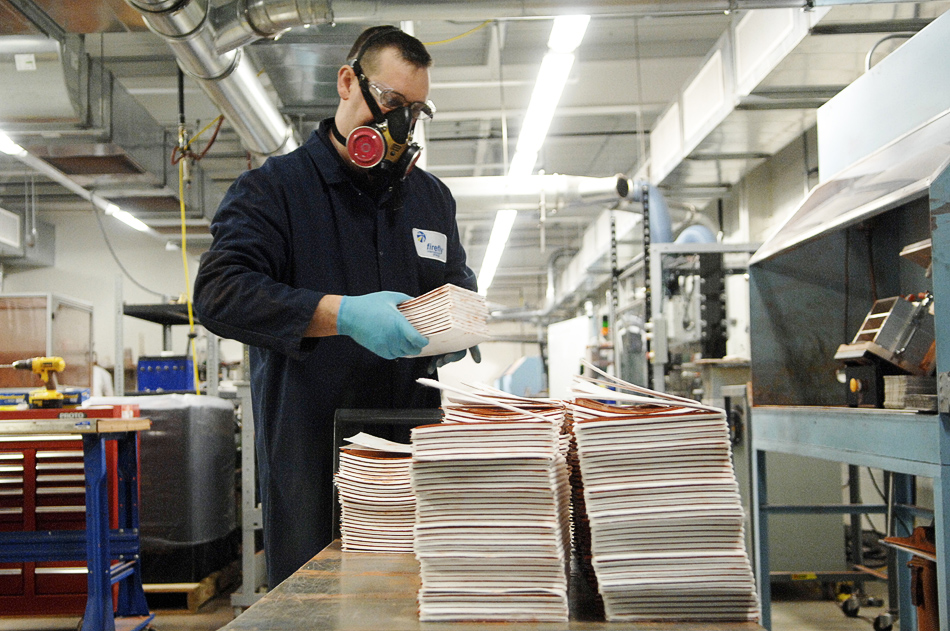 NICK SCHNELLE/JOURNAL STAR  Manufacturing technician David Barnett picks up a stack of negative electrodes to later pair with the positive electrodes.