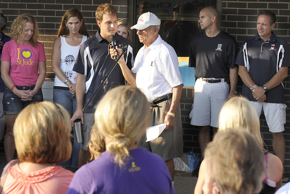 DAVID ZALAZNIK/JOURNAL STAR Former Peoria mayor Jim Maloof holds the microphone Tuesday as he talks with cancer survivor Josh Malavolti before Malavolti leaves with the rest of the St. Jude runners for his tenth Memphis-Peoria run to raise funds for the St. Jude Children's Research Hospital.