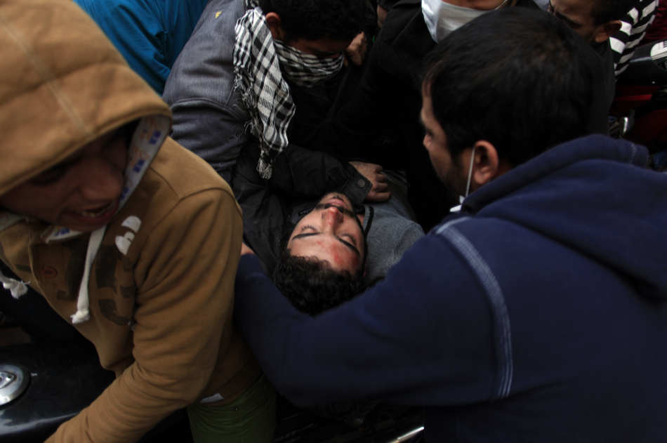 Egyptian protesters evacuate an injured man during clashes near Tahrir Square, Cairo, Egypt, Friday, Jan. 25, 2013. Egyptian opposition protesters are gathering in Cairo's Tahrir Square to mark the second anniversary of the uprising that toppled Hosni Mubarak's autocratic regime. (AP Photo/Khalil Hamra)