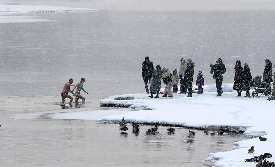 A couple walk out of the ice cold water of the Moskva River after taking a bath, in the Kolomenskoye park on the outskirts of Moscow, Russia, Saturday, Jan. 19, 2013. Thousands of Russian Orthodox Church followers plunge into icy lakes and rivers during Friday and Saturday to mark the upcoming Epiphany, cleansing themselves with water deemed holy for the day. Over night temperatures dropped to around -10 C ( 14 F) in Moscow temperatures. (AP Photo/Mikhail Metzel)