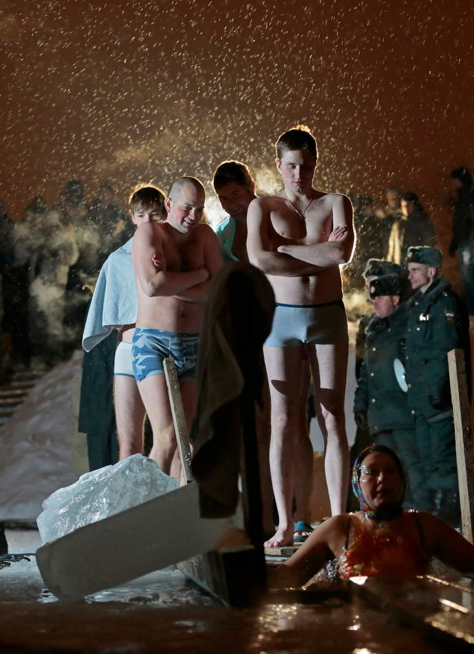 People stand in a queue to the bath of the ice cold water as they take the bath in the ice hole of the pound in the Kolomenskoye park on the outskirts of Moscow, Russia, Saturday, Jan. 19, 2013. Thousands of Russian Orthodox Church followers plunged Friday and Saturday into icy rivers and ponds across the country to mark the upcoming Epiphany, cleansing themselves with water deemed holy for the day. Water that is blessed by a cleric on Epiphany is considered holy and pure until next year's celebration, and is believed to have special powers of protection and healing. The Russian Orthodox Church follows the old Julian calendar, according to which Epiphany falls on Jan.19. Moscow temperatures on Saturday night dropped to -15 C ( 5 F). (AP Photo/Mikhail Metzel)
