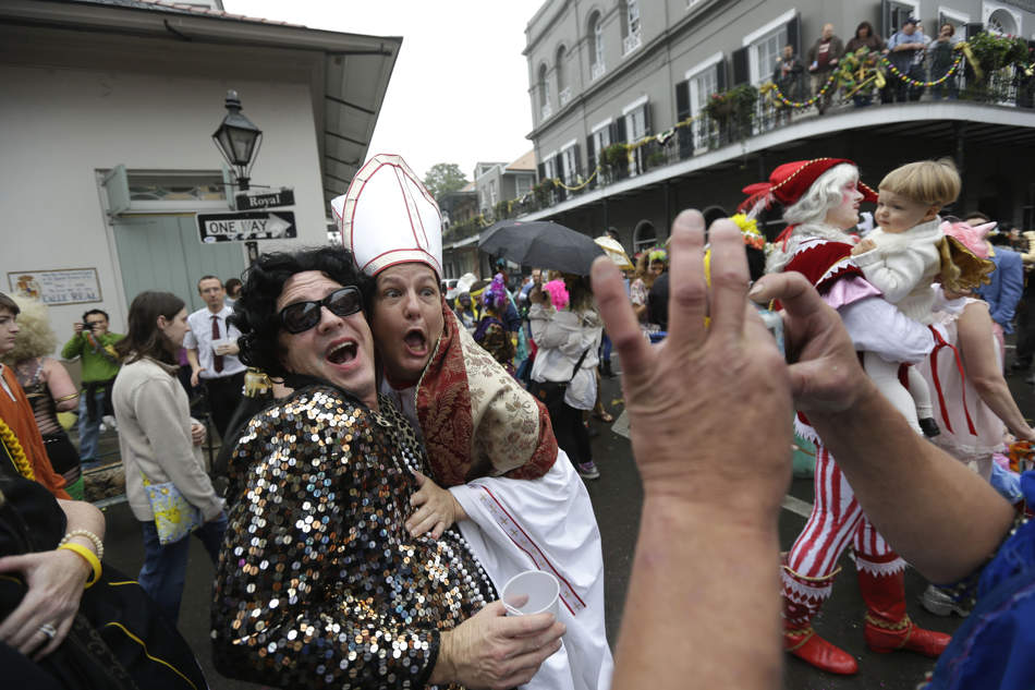 A man dressed as the Pope revels with other costumed people during Mardi Gras in the French Quarter of New Orleans, Tuesday, Feb. 12, 2013. (AP Photo/Gerald Herbert)