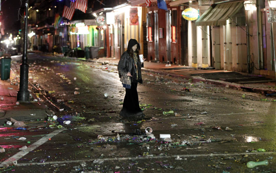 A woman walks alone on Bourbon Street in the early morning of Ash Wednesday, the day after Mardi Gras, in the French Quarter of New Orleans, Wednesday, Feb. 13, 2013. The city has begun to clean up after Mardi Gras came to a close at midnight, with Ash Wednesday ushering in the solemn season of Lent. (AP Photo/Gerald Herbert)