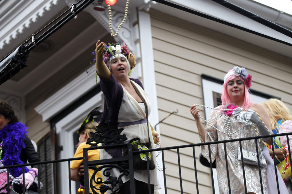 Revelers throw beads from a balcony as the Society of Saint Anne walking parade marches by in the Bywater section of New Orleans during Mardi Gras day, Tuesday, Feb. 12, 2013. (AP Photo/Gerald Herbert)