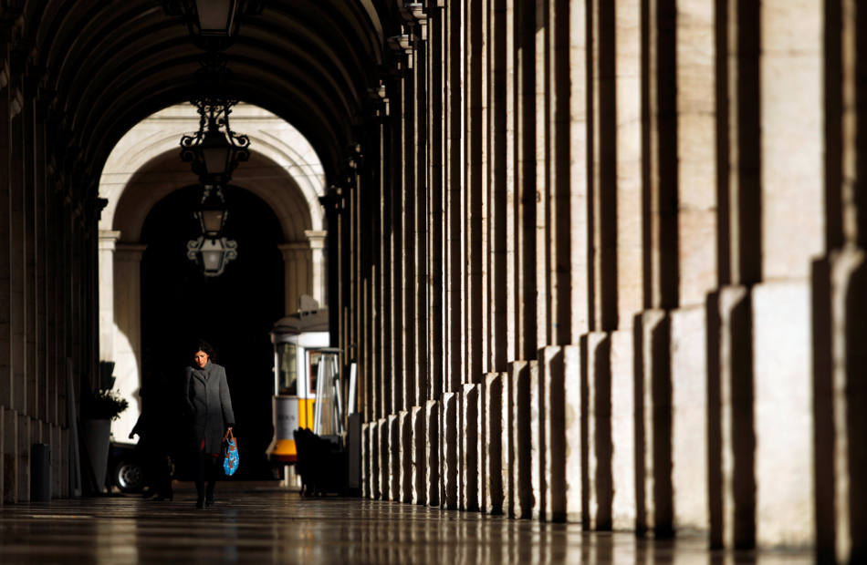 A woman walks along an arcade located in Comercio square in downtown Lisbon, Tuesday, Feb. 5, 2013. (AP Photo/Francisco Seco)
