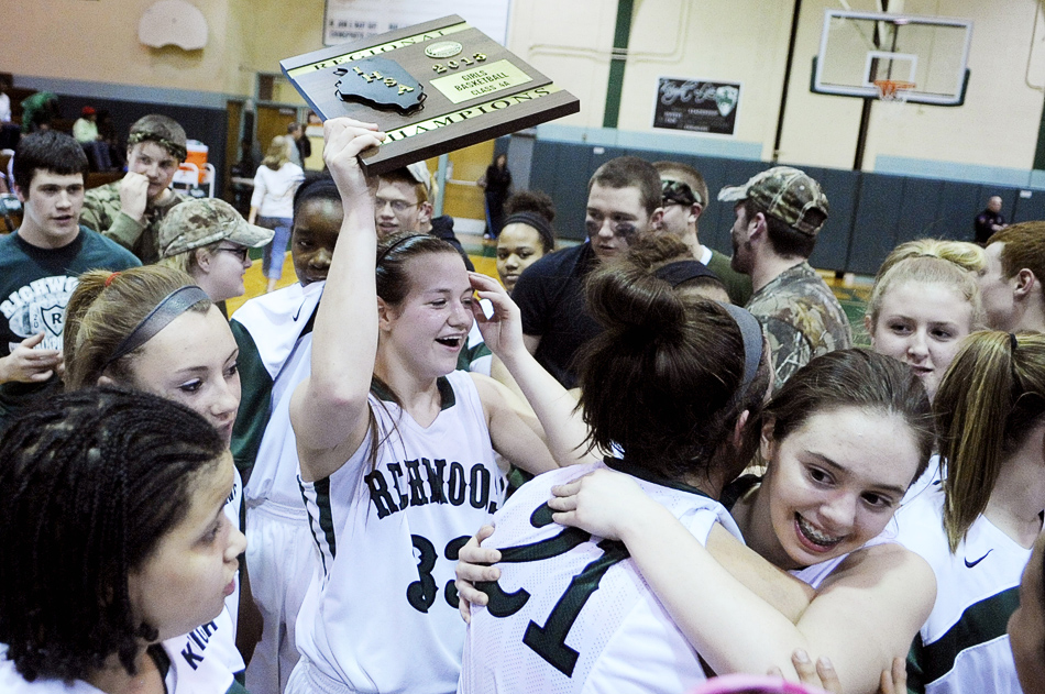 NICK SCHNELLE/JOURNAL STAR  Maddie Pierce (33) of Richwoods holds up a winning trophy as the rest of her team celebrates after defeating United Township, 57-42, on Friday at a Class 4A Regional Championship game at Richwoods High School.