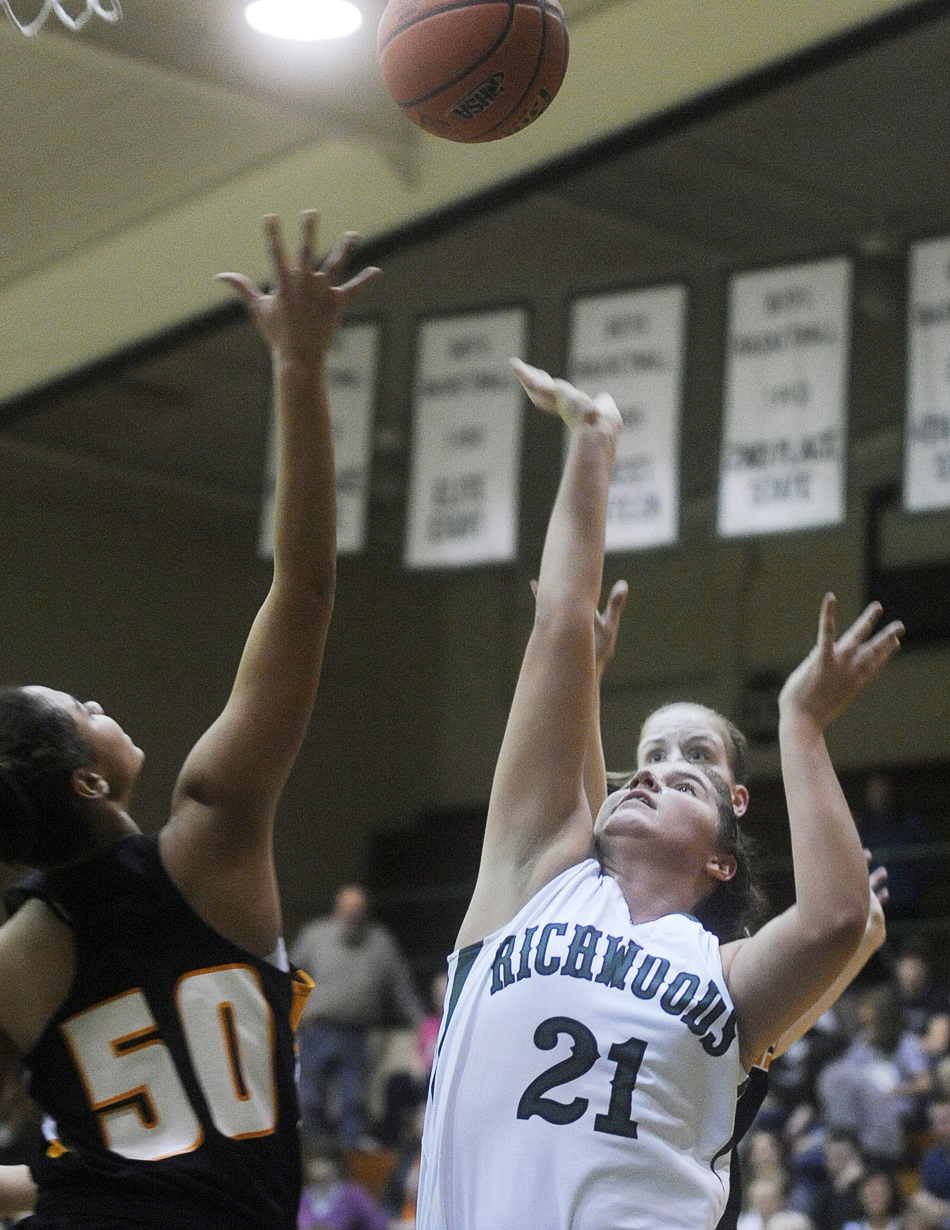 NICK SCHNELLE/JOURNAL STAR  Gabby Cunningham (21) of Richwoods shoots the ball past United Township's Jada Harris (50) on Friday at a Class 4A Regional Championship game at Richwoods High School. Richwoods defeated United Township 57-42.