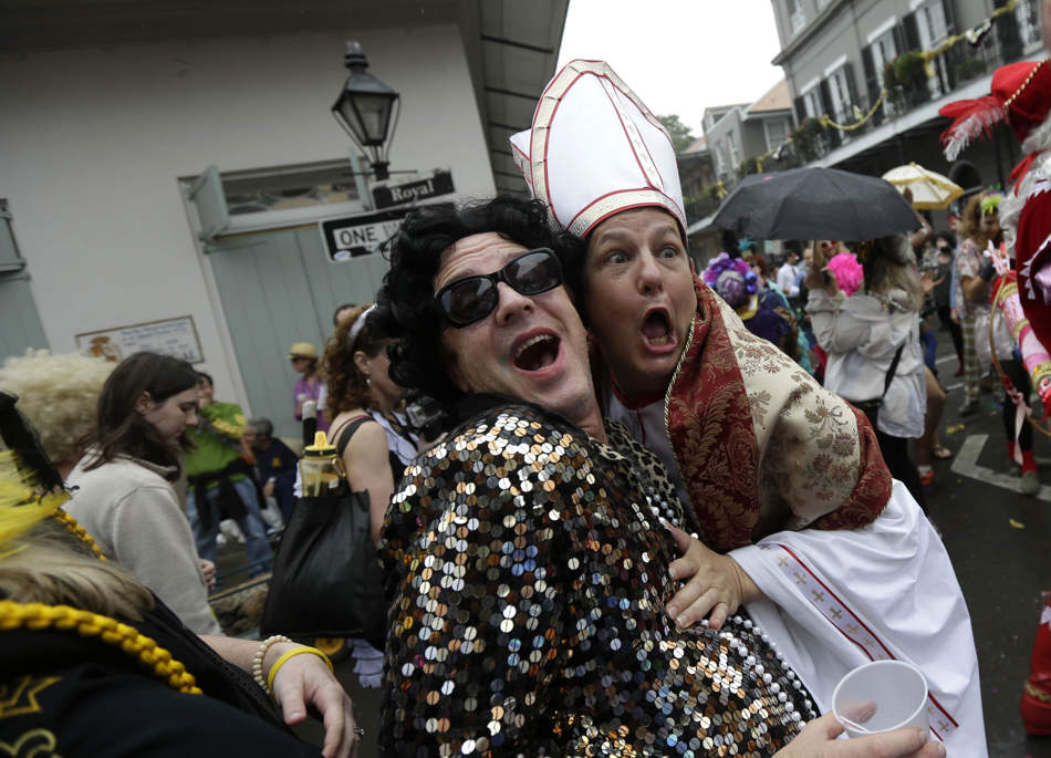 A man dressed as the Pope revels with other costumed people during Mardi Gras in the French Quarter of New Orleans, Tuesday, Feb. 12, 2013. Despite threatening skies, the Mardi Gras party carried on as thousands of costumed revelers cheered glitzy floats with make-believe monarchs in an all-out bash before Lent.   Crowds were a little smaller than recent years, perhaps influenced by the forecast of rain. Still, parades went off as scheduled even as a fog settled over the riverfront and downtown areas. (AP Photo/Gerald Herbert)