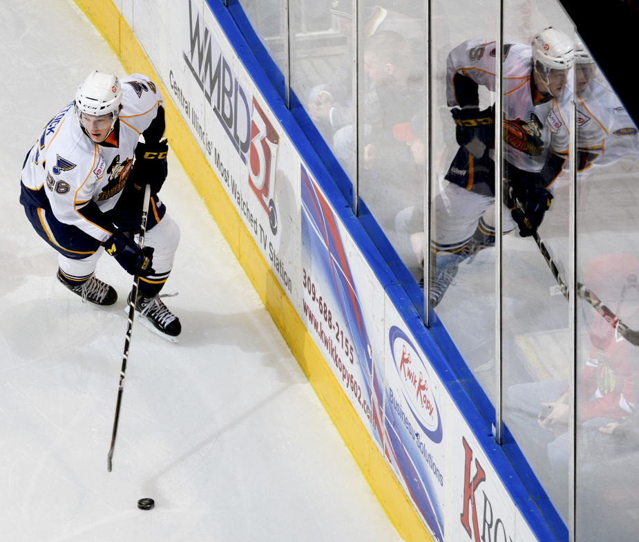 RON JOHNSON/JOURNAL STAR  Tyler Shattock of the Rivermen is reflected in the glass as he moves the puck up the ice.