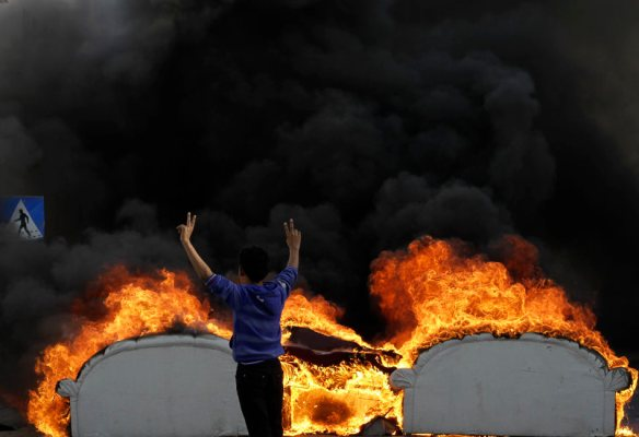 A Bahraini anti-government protester flashes the victory sign as he stands behind old furniture set on fire in a street in Malkiya, Bahrain, Tuesday, Feb. 26, 2013. Protests are being held in opposition villages nationwide, demanding the government release for burial the body of a 20-year-old who died last week from injuries sustained during earlier clashes with police. (AP Photo/Hasan Jamali)