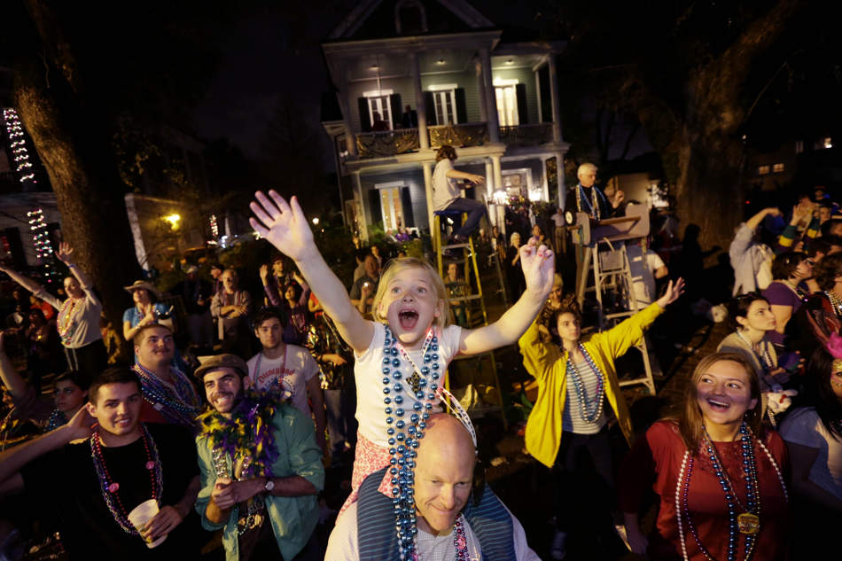 Addison Moran, 7, yells for beads and trinket from the shoulders of her father Paul Moran during the Krewe of Bacchus Mardi Gras parade in New Orleans, Sunday, Feb. 10, 2013. (AP Photo/Gerald Herbert)
