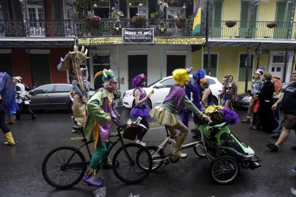 Rivelers pass a sign critical of NFL Commissioner Roger Goodell during Mardi Grasin the French Quarter  in New Orleans, Tuesday, Feb. 12, 2013. (AP Photo/Gerald Herbert)
