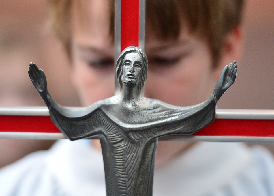 FRED ZWICKY/JOURNAL STAR Alter boy Noah Chase, 9, bows his head as he prepares to carry the cross at St. Thomas the Apostle Catholic Church in Peoria Heights for Ash Wednesday services over the noon hour. The event marks the first day of Lenten season.