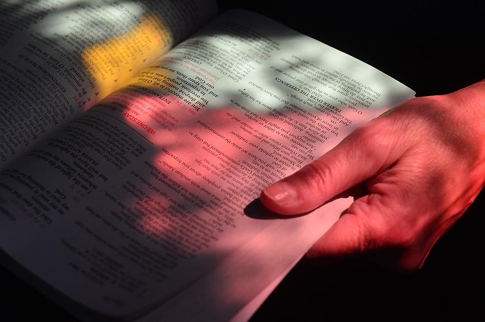 FRED ZWICKY/JOURNAL STAR Dappled light from the stained glass windows light up the prayer book of Marie Brien as people gather for Ash Wednesday services at St. Thomas the Apostle Catholic Church in Peoria Heights.