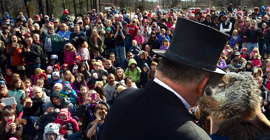 "Garner Mayor Ronnie Williams ""listens"" as resident groundhog, Mortimer, ""whispers"" his prediction for either six more weeks of winter or an early spring in front of a large crowd, Saturday, Feb. 2, 2013, in Garner, N.C. (AP Photo/The News & Observer, Chuck Liddy)"
