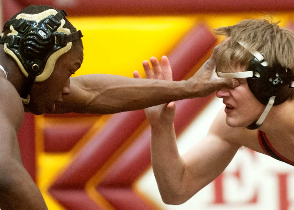 NICK SCHNELLE/JOURNAL STAR   Washington's Randy Meneweather, left, sticks his hand into the face of Pekin's Jordan Bowman during the 132 lb. championship match at the Mid-Illini Conference Wrestling Tournament at East Peoria High School. Meneweather went on to win the match.