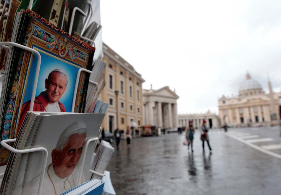 Postcards of Pope Benedict XVI, bottom, and late Pope John Paul II, are displayed outside a kiosk with St. Peter's Basilica in the background, at the Vatican, Monday, Feb. 11, 2013. Pope Benedict XVI announced Monday that he would resign Feb. 28 — the first pontiff to do so in nearly 600 years. The decision sets the stage for a conclave to elect a new pope before the end of March. (AP Photo/Gregorio Borgia)