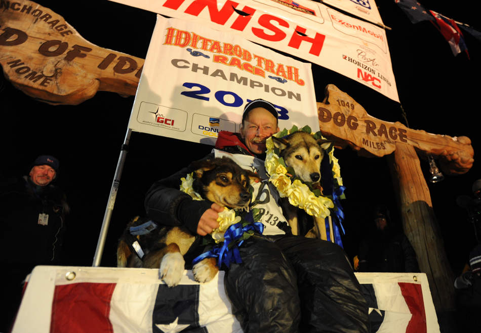 Mitch Seavey became the oldest winner, a two-time Iditarod champion when he drove his dog team under the burled arch in Nome on Tuesday evening, March 12, 2013. He sits with his two lead dogs, Tanner, left and Taurus, right. (AP Photo/The Anchorage Daily News, Bill Roth)  LOCAL TV OUT (KTUU-TV, KTVA-TV) LOCAL PRINT OUT (THE ANCHORAGE PRESS, THE ALASKA DISPATCH)