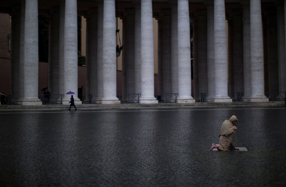 A barefoot faithful kneels in prayer in St. Peter's Square as cardinals are gathered in the Sistine Chapel for the second day of the conclave to elect a new pope, at the Vatican, Wednesday, March 13, 2013. Cardinals are returning to the Sistine Chapel for a second day of voting to choose a new pope after their first ballot yielded no winner and a great plume of black smoke emerged from the Sistine Chapel chimney. (AP Photo/Emilio Morenatti)