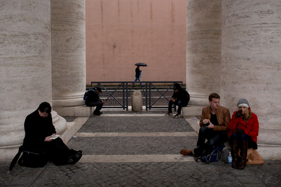 Visitors stand under the Bernini Colonnade in St. Peter's Square at the Vatican, Wednesday, March 13, 2013. Cardinals remained divided over who should be pope on Wednesday after three rounds of voting, an indication that disagreements remain about the direction of the Catholic church following the upheaval unleashed by Pope Benedict XVI's surprise resignation. (AP Photo/Emilio Morenatti)