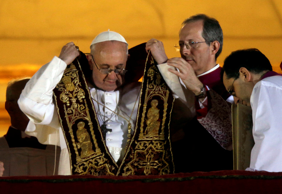 Pope Francis puts on his sash from the central balcony of St. Peter's Basilica at the Vatican, Wednesday, March 13, 2013. Cardinal Jorge Bergoglio who chose the name of  Francis, is the 266th pontiff of the Roman Catholic Church. (AP Photo/Gregorio Borgia)