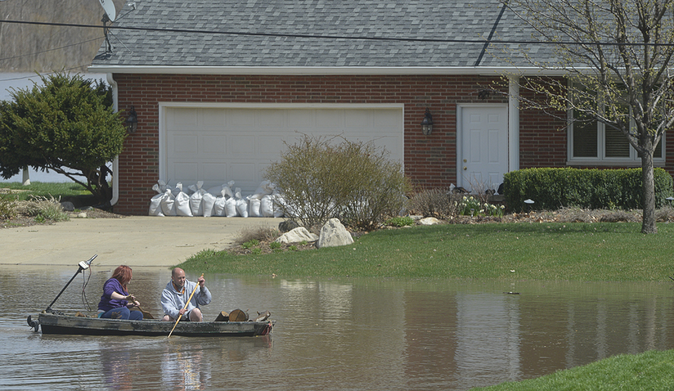 RON JOHNSON/JOURNAL STAR  Chad Keedy and stepdaughter Jordan DeBolt, 15, paddle through flood waters in their neighborhood along Oak Lawn Steet in Chiilicothe on Saturday after firewood stacked in their lawn began to float away.