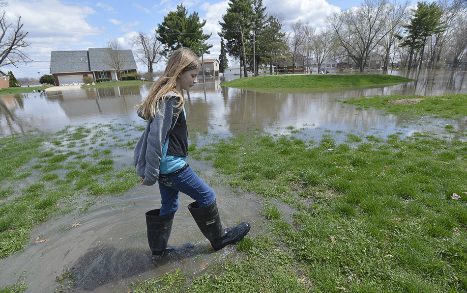 RON JOHNSON/JOURNAL STAR  Kaitlyn Keedy, 10, walks through a flooded portion of her neighborhood along Oak Lawn Steet in Chiilicothe on Saturday