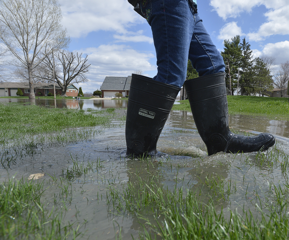 RON JOHNSON/JOURNAL STAR  Kaitlyn Keedy, 10, walks through a flooded portion of her neighborhood along Oak Lawn Steet in Chiilicothe on Saturday.