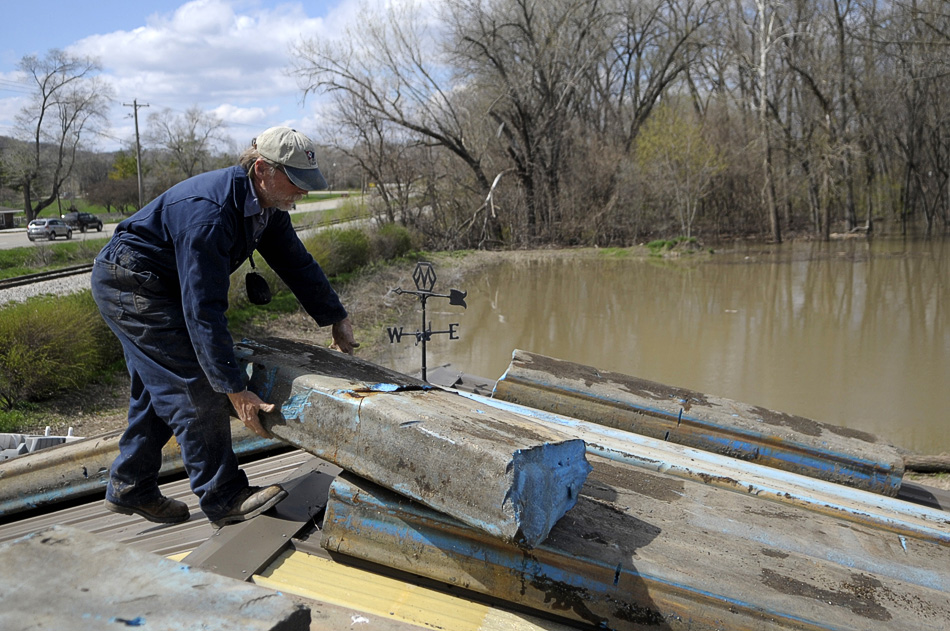 NICK SCHNELLE/JOURNAL STAR  Ron Johnson, harbor master of the Illinois Valley Yacht & Canoe Club, helps move foam billets so they don't float away in the boat yard on Saturday in preparation for record flood levels along the Illinois River.