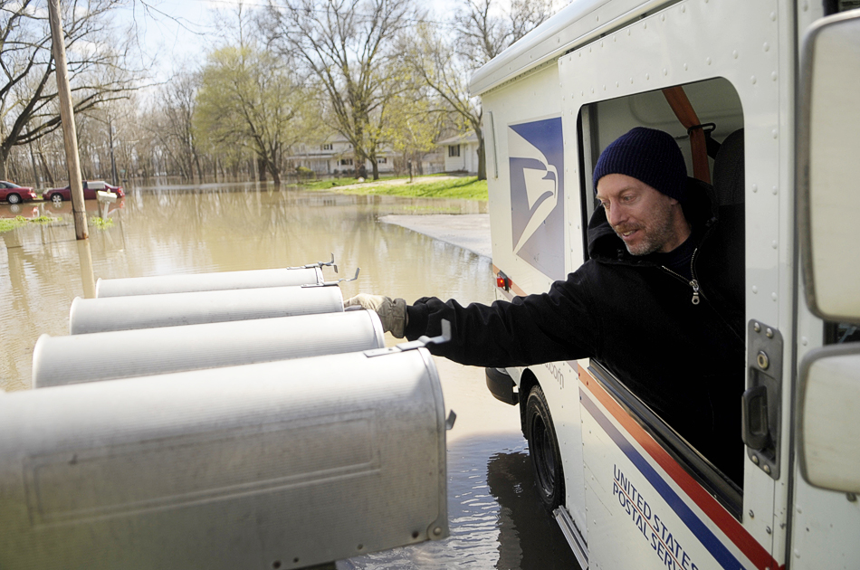 "NICK SCHNELLE/JOURNAL STAR  Rural mail carrier Jeffrey Justen delivers mail at the intersection of Cross Street and Valley Shore Drive in an area just south of Mossville on Saturday as flood water rises along the Illinois River. Justen said that due to the water he has to modify his route. ""I don't go in uncharted waters,"" he said."