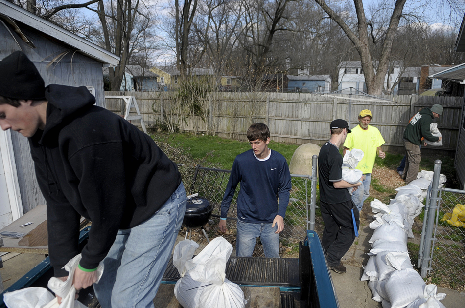 NICK SCHNELLE/JOURNAL STAR  A group, including Illinois Central Valley High School students, helps stack sandbags around the home of Dixie Meeks, left, on Saturday in an area just south of Mossville as flood water rises along the Illinois River.