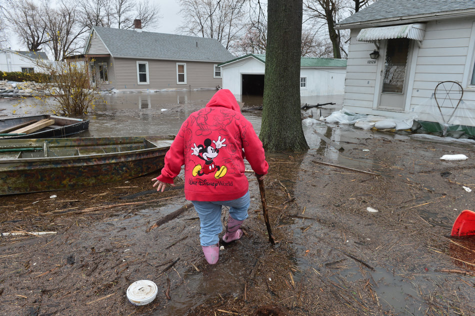 FRED ZWICKY/JOURNAL STAR Living beside the river means living in the river for many residents living along Riverview Road south of Chillicothe. A resident walks through the muck to show off her flooded basement.