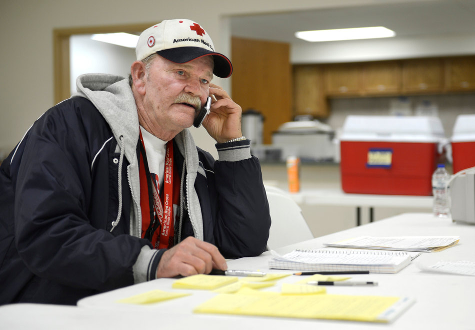 DAVID ZALAZNIK/JOURNAL STAR Red Cross shelter manager Walt Lockhart calls in an estimate of supply needs Tuesday at River's Edge United Methodist Church in Spring Bay Tuesday. Lockhart has work in several hurricanes on his resume.