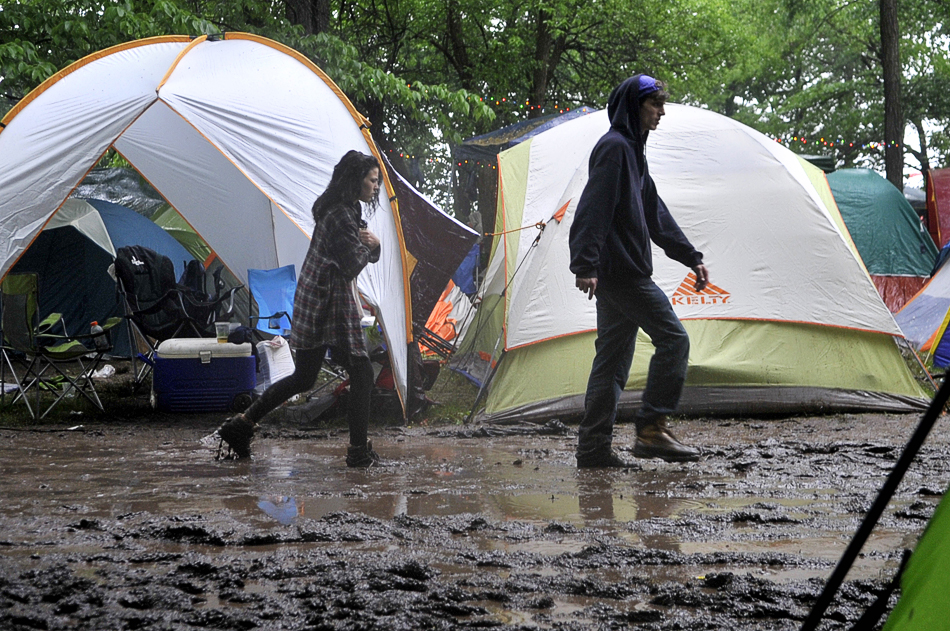 NICK SCHNELLE/JOURNAL STAR  Festivalgoers trek through the mud on Sunday at Summer Camp in Chillicothe.
