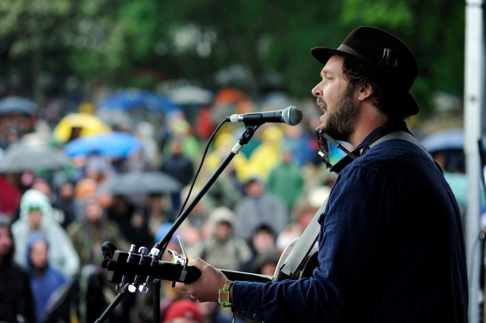 DAVID ZALAZNIK/JOURNAL STAR Delavan native Cody Diekhoff, with a stage name of Chicago Farmer, sings to a loyal crowd standing in a steady rain at Summer Camp at Three Sisters Park in Chillicothe Saturday.
