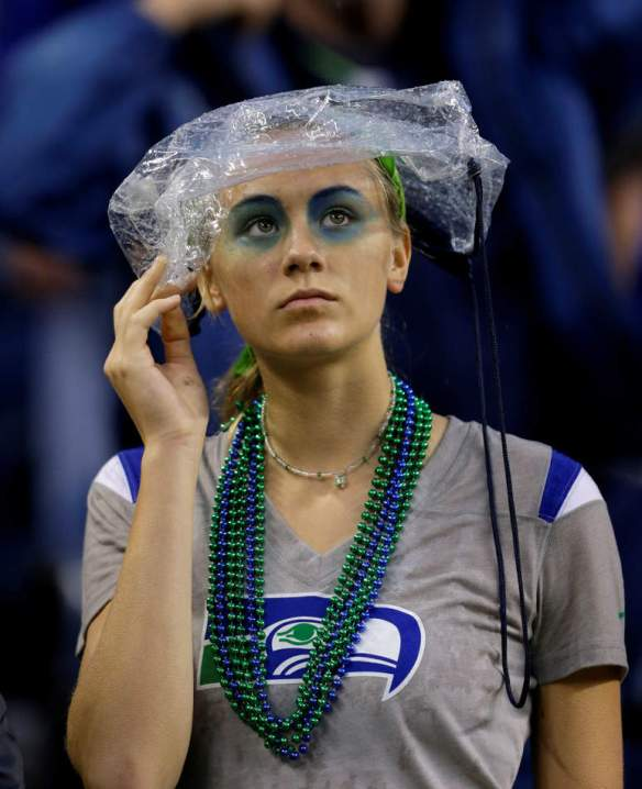 A Seattle Seahawks fan wears an official NFL football security bag on her head during a severe weather delay in the first half of an NFL football game between the Seattle Seahawks and the San Francisco 49ers, Sunday, Sept. 15, 2013, in Seattle. (AP Photo/Elaine Thompson)