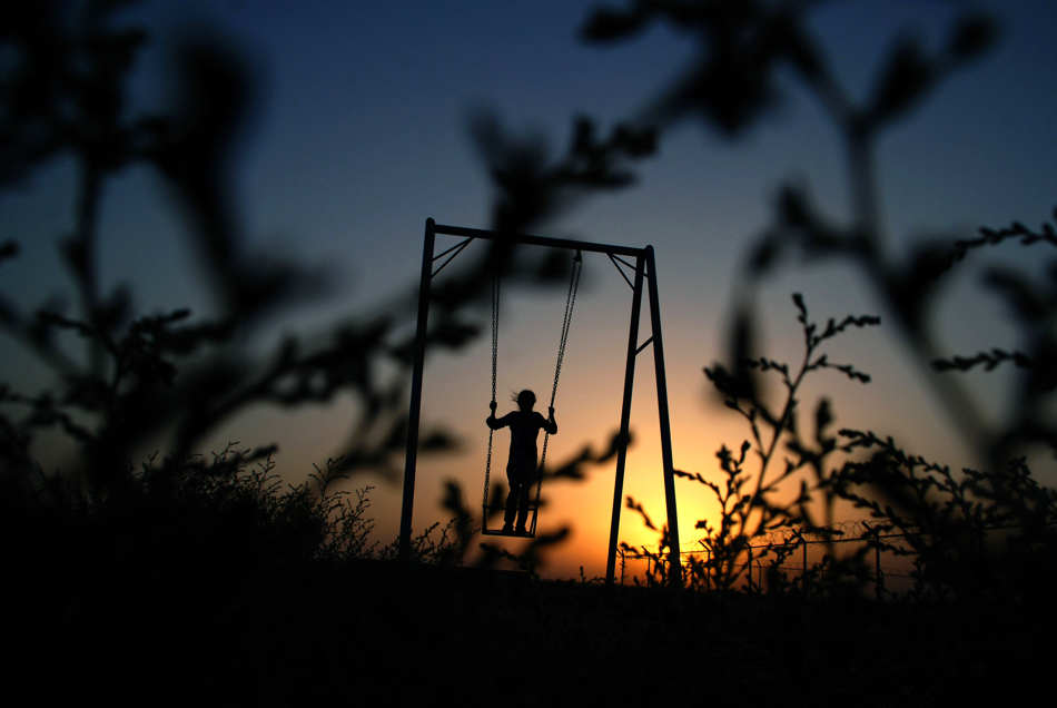 An Afghan girl plays on a swing in a playground at sunset on the outskirts of Mazar-e-Sharif north of Kabul, Afghanistan, Friday, Sept. 13, 2013.(AP Photo/Mustafa Najafizada)