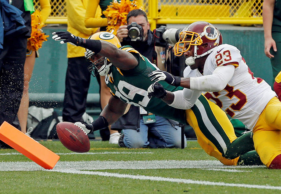 Washington Redskins' DeAngelo Hall (23) knocks Green Bay Packers' James Jones (89) out of bounds after a catch during the first half of an NFL football game Sunday, Sept. 15, 2013, in Green Bay, Wis. (AP Photo/Mike Roemer)