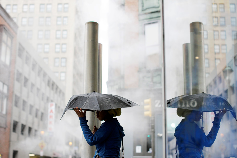 A woman shields herself with an umbrella during an afternoon rainstorm Friday, Oct. 11, 2013, in Philadelphia. The exhibition is scheduled to run through Jan. 5, 2014. (AP Photo/Matt Rourke)