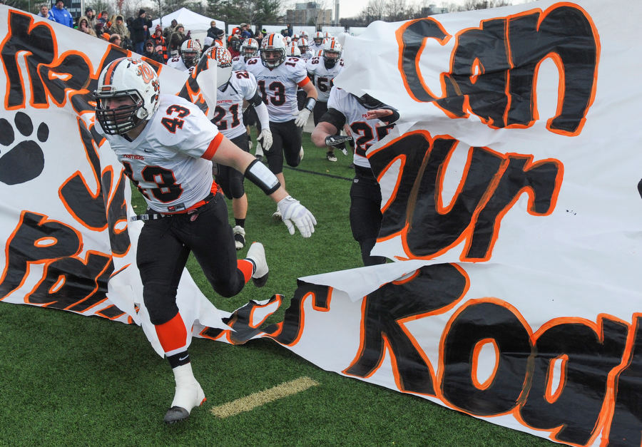 RON JOHNSON/JOURNAL STAR  Washington's Chris Friend breaks through the banner with teammates before the kickoff of Saturday's Class 5A semifinal game.