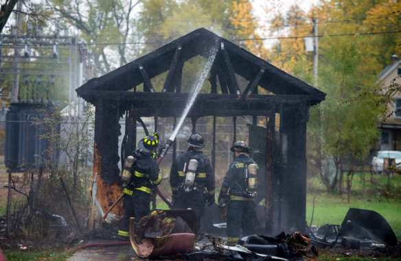 FRED ZWICKY/JOURNAL STAR Peoria firefighters spray the remains of a garage, as well as a house at 2700 W. Malone, both damaged by a fire on Nov. 5 over the lunch hour.