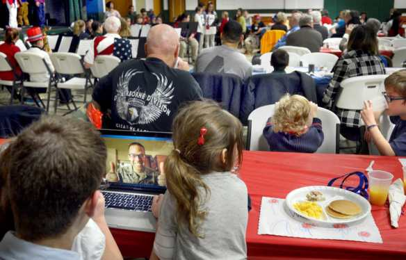 DAVID ZALAZNIK/JOURNAL STAR  Jay Zalazinski gives a thumbs-up from the computer screen to his children, with whom he is communicating by Skype from South Korea, on Nov. 7 during the Holy Family School free breakfast for area veterans and their families. Zalazinski is serving with the U.S. Air Force in South Korea. More than three dozen veterans registered for the fifth annual breakfast that included music by the school's band and choir.