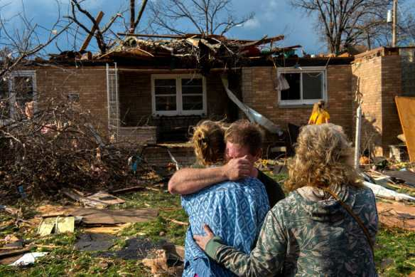 FRED ZWICKY/JOURNAL STAR Ray Baughman, facing, embraces family shortly after his home was destroyed by a tornado that left a path of devastation through the north end of Pekin on Nov. 17.