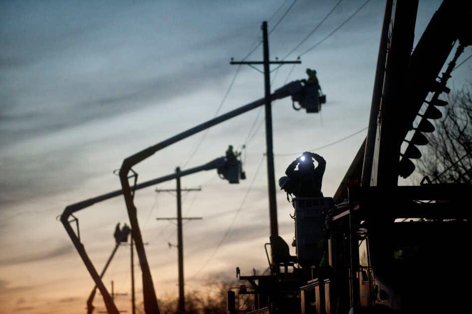 JUSTIN WAN/JOURNAL STAR A worker turns on the headlight on his hardhat on Nov. 19 as members of a crew repair power lines knocked down by a Nov. 17 storm on W. Muller Road in East Peoria.