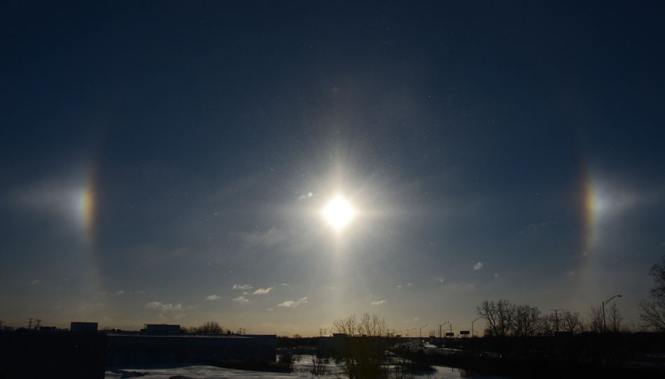 A sun dog is seen over the Jane Addams tollway in Arlington Heights, Ill., on Monday morning, Jan. 27, 2014. Sun dogs are caused by sunlight passing through ice crystals in the upper atmosphere. (AP Photo/Daily Herald, Jeff Knox) MANDATORY CREDIT, MAGS OUT