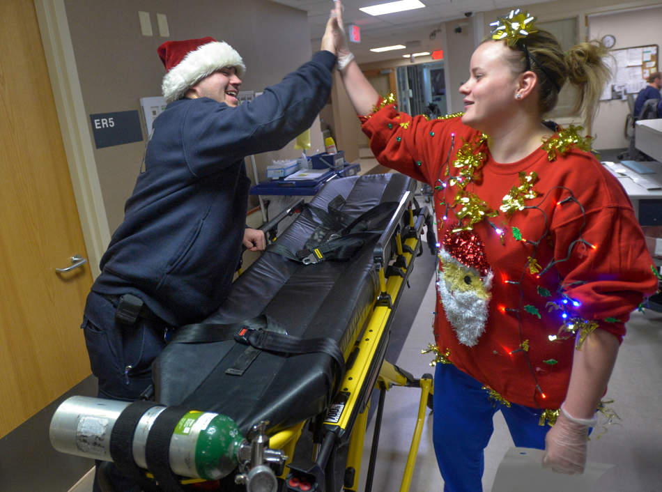 RON JOHNSON/JOURNAL STAR   Methodist EMTs Mallory Mark, right, and Anthony Hoopingarner share a high-five during their Christmas Day shift at work.