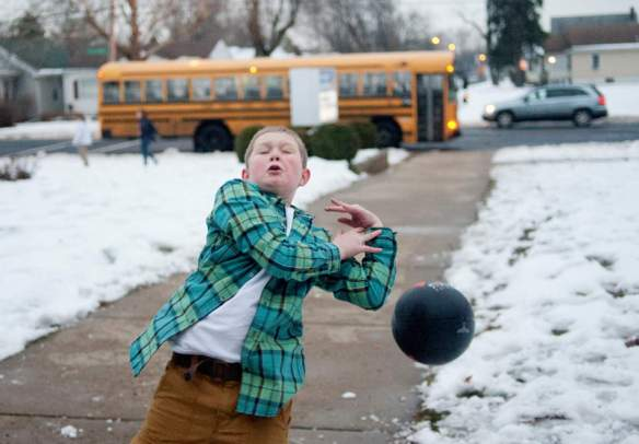 JUSTIN WAN/JOURNAL STAR Peoria resident Quenton Thomas Chambers, 10, tries to catch a ball without success as he and other boys play ball while waiting for school bus at the end of the after-school program on Dec. 19 at Von Steuben Middle School.